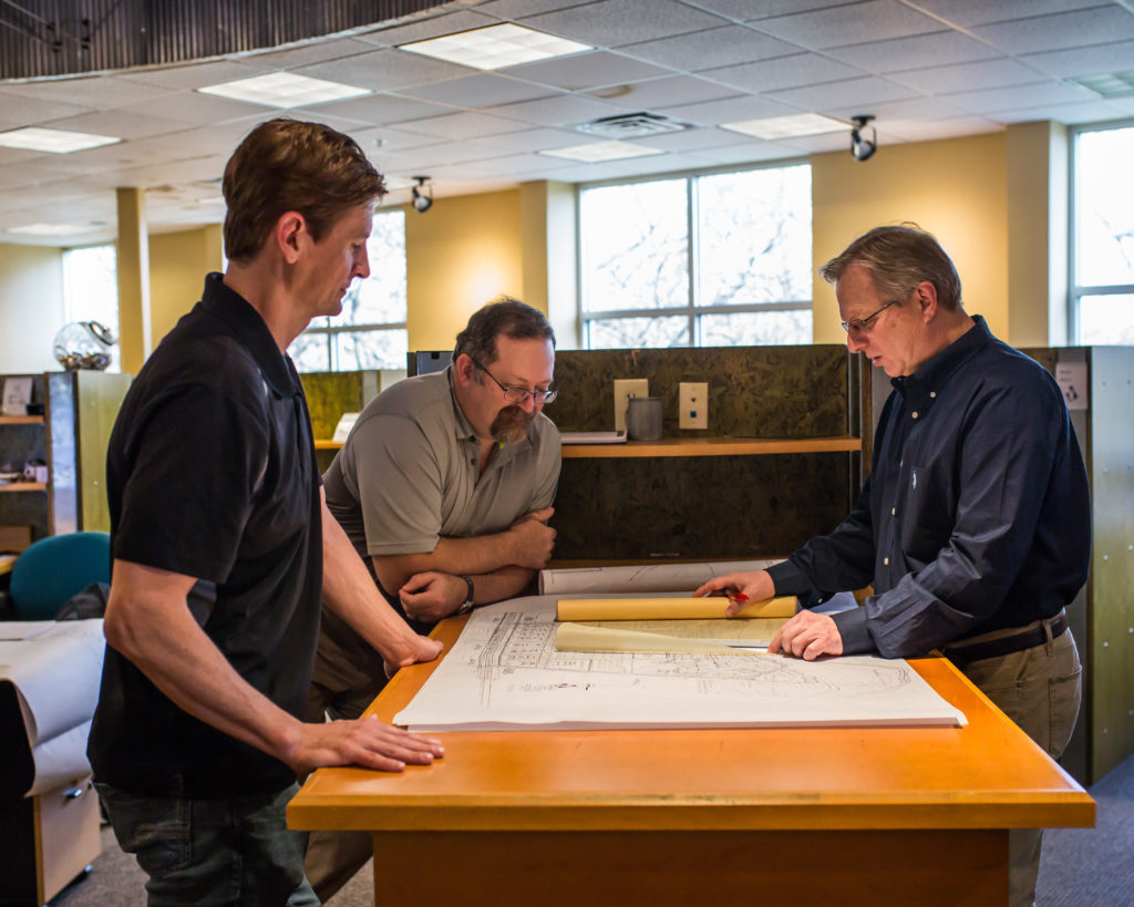 General contractor, architect and project manager gathered around a drafting table discussing plans for commercial property build