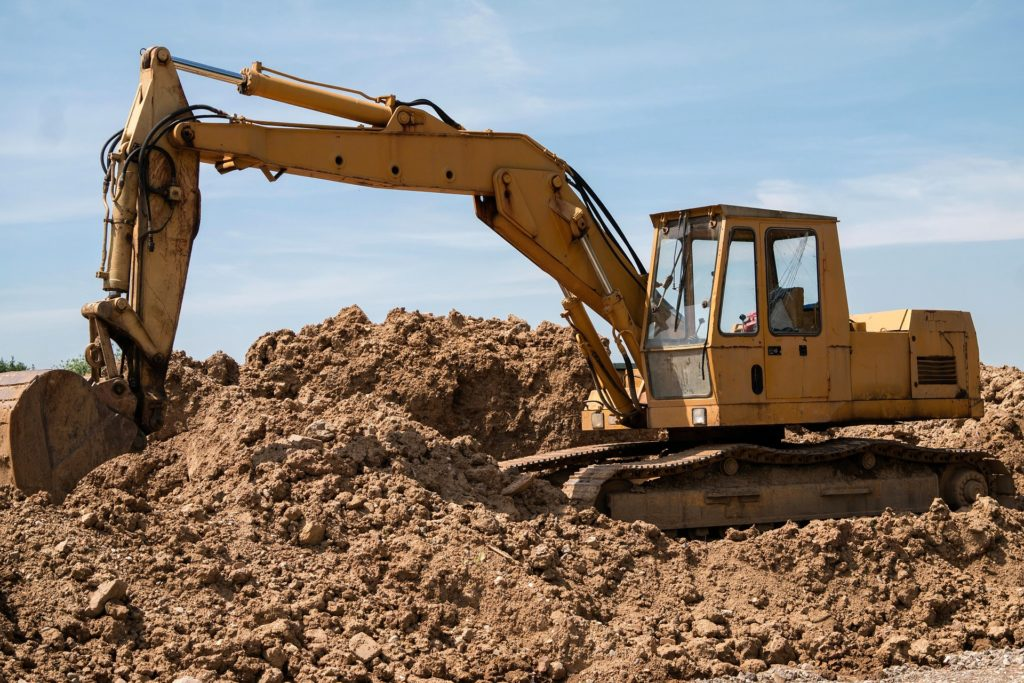 Excavator surrounded by dirt, preparing lot for commercial healthcare facility
